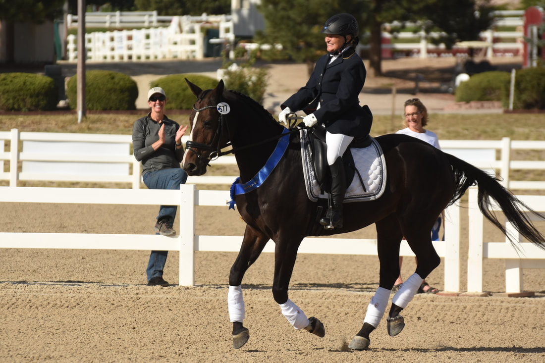 Author M.J. Evans and her horse competing in Dressage